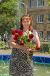 A woman with a bouquet of red flowers stands on the background of a fountain.