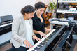 young women playing piano
