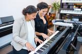 young women playing piano - 213252534
