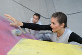 fit woman rock climbing indoors at the gym - 213255145