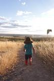 Menino de chapéu correndo pelo campo