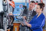 Mechanics examining motorcycle - 213257932