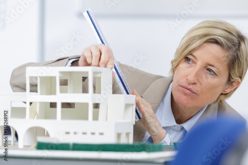 Foto Murales beautiful businesswoman with house model made from scale
