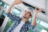 worker putting back the ceiling plaster board cover - 213269167