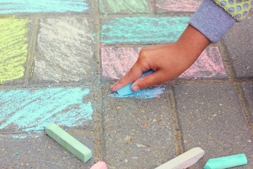 The child paints with chalk on the asphalt.