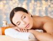 canvas print picture - wellness, spa and beauty concept - close up of beautiful woman with bottle of massage or essential oil over holidays lights background