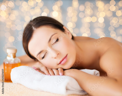 canvas print picture wellness, spa and beauty concept - close up of beautiful woman with bottle of massage or essential oil over holidays lights background