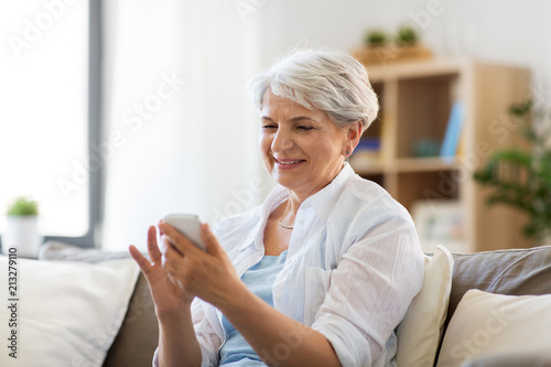 Leinwanddruck Bild technology, communication and people concept - happy senior woman with smartphone at home