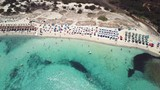 Aerial view of an emerald and transparent mediterranean sea with a white beach full of beach umbrellas and tourists who relax and take a bath. Gulf of the Great Pevero, Emerard coast , Sardinia, Italy - 213294549