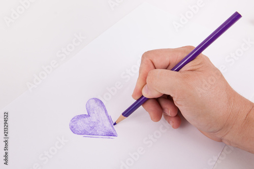 Ręka szkicuje purpurowego serce z kolorystyki kartografuje ołówek na białym tle