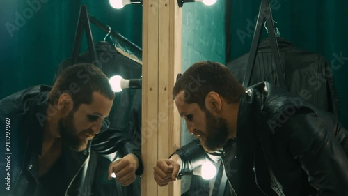 Side view of man in leather jacket preparing for concert and sniffing drugs in front of mirror in dressing room
