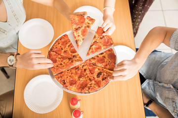 Hands taking and sharing pepperoni pizza on wooden table