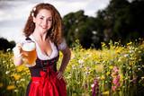 junge Frau im Dirndl mit Bier vor Blumenwiese