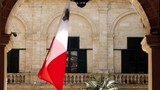 Big Maltese flag flaps in wind at Palace Armoury - 213315134