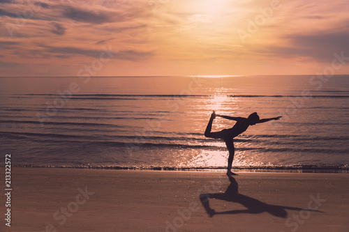 Fototapeta Asian women play yoga on a sand beach by the sea background in the morning. Exercise and meditation concept.