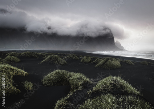Fotobehang Zwart Beautiful seascape in Iceland which looks like a moon landscape with green grass dunes in the foreground, a black sand beach in the middle ground and mountains covered in clouds in the background