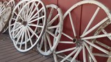 Several old Wooden Wagon wheels all lined up along a wall - 213329766