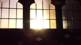 Set in an ancient church in England, this video is a pan shot from the church door to the porch. The light from the setting sun is pouring in. - 213331395