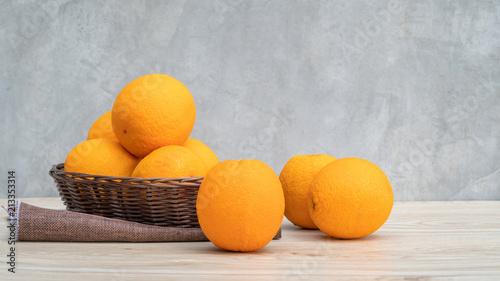 Pomarańcze owocowe w koszu na drewnianym stole.