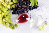 Red Wine and white wine with grapes and glasses on rustic background.