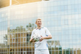 Portrait of a football player against the background of the building in white uniform. Holds a soccer ball. His team won the championship - 213371746