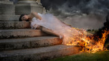 Bride with wedding dress burning next to the stairs of a temple with storm weather. scene of pain, suffering and abandonment