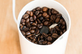 Coffee beans in a modern coffee grinder closeup on wooden background. Roasted aromatic coffee top view. - 213390338
