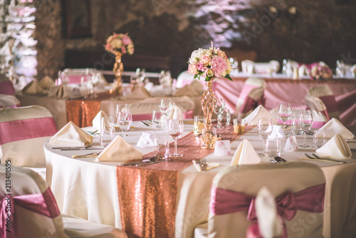 wedding table with exclusive floral arrangement prepared for reception, wedding or event centerpiece in rose gold colour