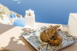 Fried shrimps on traditional plate with famous blue church of oia background in Oia, Santorini, Greece - 213416135