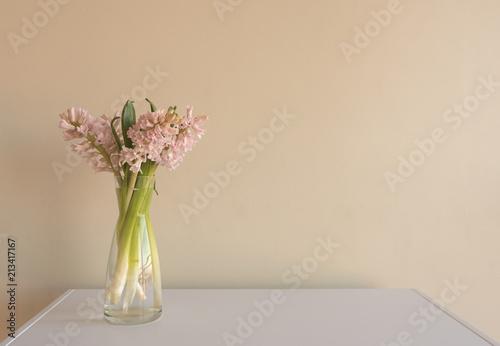 Zbliżenie miękkich różowy Hiacynty w szklanym wazonie na białym stole z beżową ścianą (selektywne focus)
