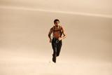 Muscular man running on sand dunes - 213417372
