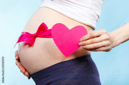 Pregnant woman holding heart and touching her belly with pink ribbon, concept of expecting for newborn girl