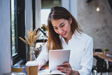 Asian casual woman freelancer using tablet and writing plan and smile with coffee cup in cafe restaurant,woman working outside office,digital lifestyle concept.