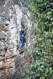 Asian boy in the helmet climbs the rock, kid rock climber sports outdoors. - 213441740