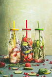 Various colorful infused water in bottles with fruits berries, cucumber, herbs and drink straws with ingredients on table, front view. Tasty summer clean beverages for  healthy lifestyle and fitness - 213465559