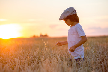 Cheerful child, boy, chasing soap bubbles in a wheat field on sunset
