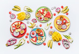 Flat lay of summer various colorful sliced tropical fruits and berries plates and bowls on white  background with ingredients, top view.  Clean and healthy lifestyle  background - 213465939