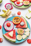 Plate with summer various colorful sliced tropical fruits and berries on white  background, top view. Clean and healthy lifestyle concept - 213465974