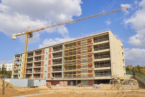 Foto Murales Industrial tower cranes at construction site, unfinished building.