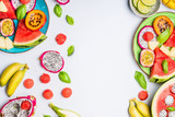 Summer clean and healthy lifestyle  background with various colorful sliced tropical fruits and berries plates and bowls on white  background, top view, frame - 213466122