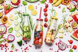 Summer clean and healthy lifestyle and fitness background with various infused water in bottles, colorful sliced ingredients: fruits, berries, vegetables, herbs on white  background, top view - 213466170
