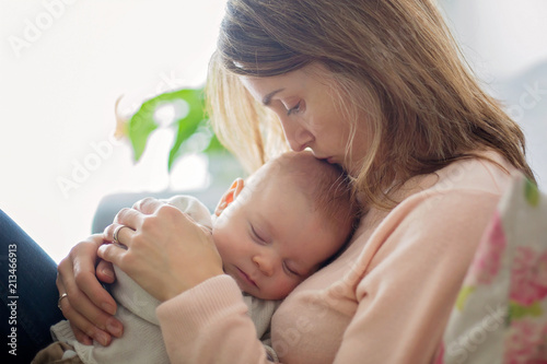 Young mother, holding tenderly her newborn baby boy - 213466913