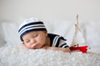 Leinwanddruck Bild - Cute baby boy, dressed in marine clothes, sleeping with wooden boat and cute little baby bunny