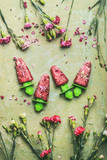 Red homemade fruits and berries ice cream or popsicles on teal rustic green table background, decorated with garden flowers, top view.  Country style summer food concept - 213467918