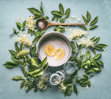 Flat lay of ingredients for seasonal traditional making of syrup and elderberry flowers: cooking pot, wooden spoon, sugar, lemon and glass jars on blue kitchen table background, top view - 213469773