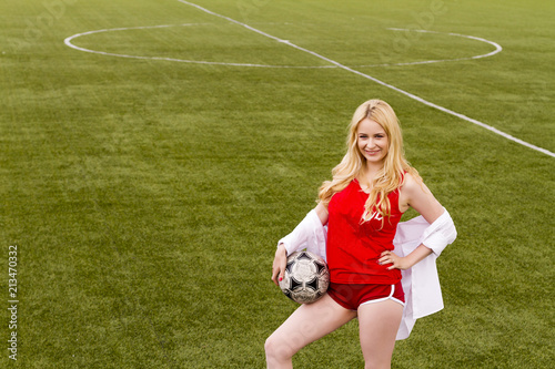 Fotobehang Voetbal Blonde with a ball on the football field in red uniform.