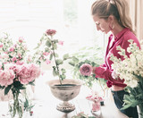 Florist women with long blond hair make beautiful big festive event classical bouquet with roses and other flowers in urn vase on table at window, lifestyle - 213470799