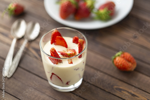 Wall mural Closed up Yogurt in glass and strawberry on a wooden background.
