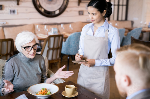 Fototapeta Senior elegant woman making an order to waitress while sitting in cafe with her son