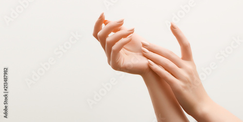 Leinwanddruck Bild Beautiful Woman Hands. Female Hands Applying Cream, Lotion. Spa and Manicure concept. Female hands with french manicure. Soft skin, skincare concept. Hand Skin Care.